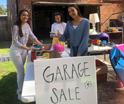 three young women setting out items on tables at a garage sale