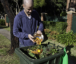 a man adding food scraps to a green waste recycling bin