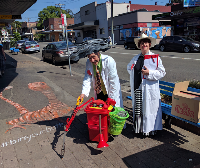 colourful characters in street theatre picking up cigarette butts