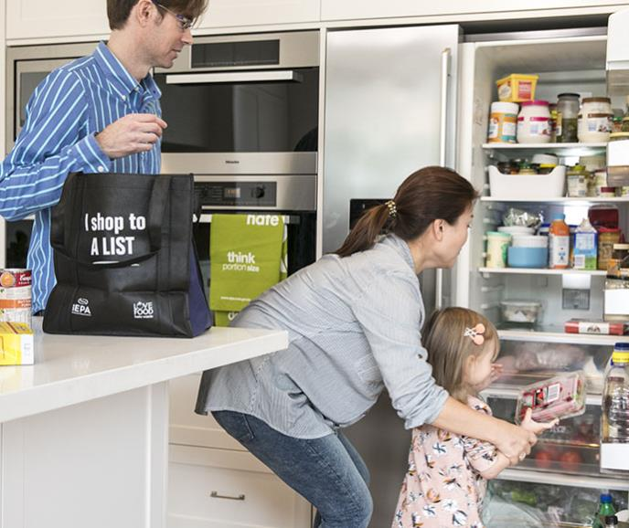 family filling the fridge with food