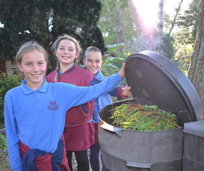 School children proudly showing off compost bins filled with organic waste