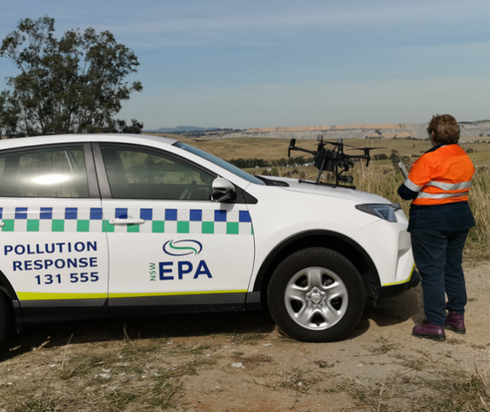 EPA officer in the field with a drone, next to an EPA car with the words Polllution Response