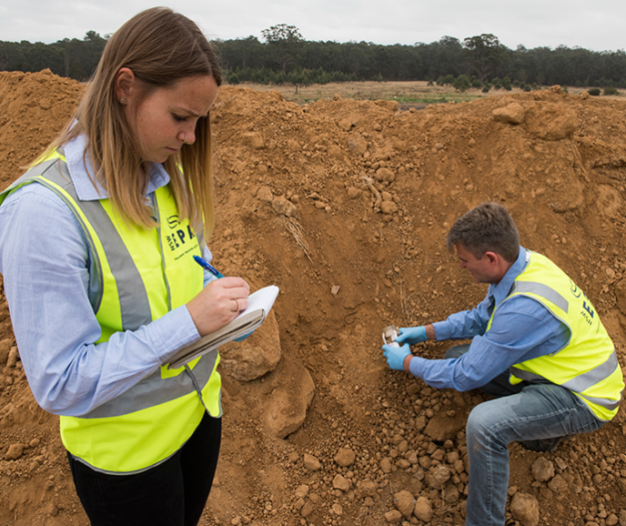 Two inspectors wearing hi-vis vests on a site inspection. The man is taking a soil sample while the woman writes in a notebook