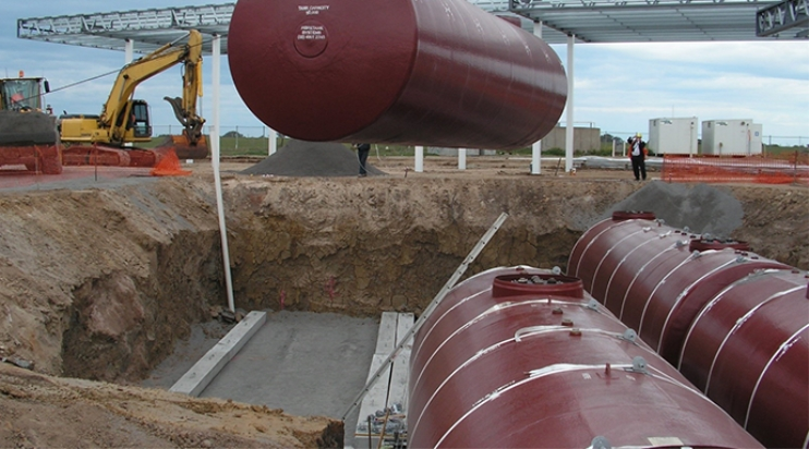 A crane lifts large storage tank into place in a pit holding two other tanks