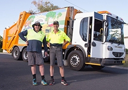 two workers beside garbage truck