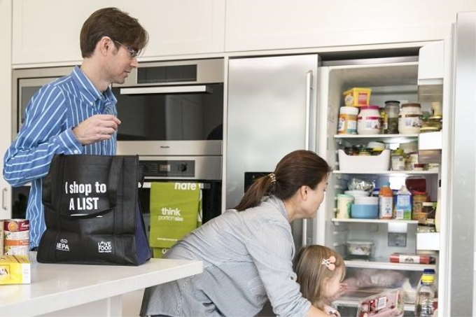 Man, woman and child in kitchen putting shopping in the refrigerator