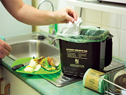 hands adding organic material to kitchen caddy